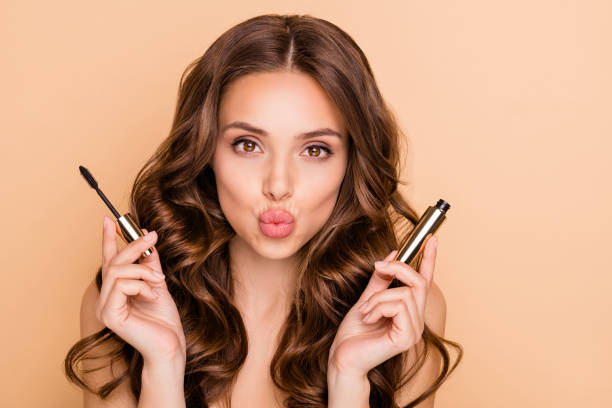 Close up photo of charming pretty girl hold mascara prepare for date look at mirror send air kisses isolated over pastel color background stock photo