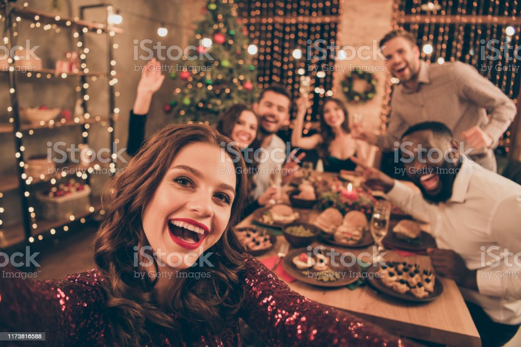 Close up photo of cheerful fellows in formal wear sit around table enjoy christmas party x-mas holidays making selfie in house full of noel decoration - Foto stock royalty-free di Adulto