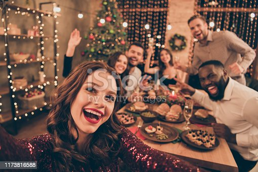 Close up photo of cheerful fellows in formal wear sit around table enjoy, christmas party x-mas holidays making selfie in house full of noel decoration