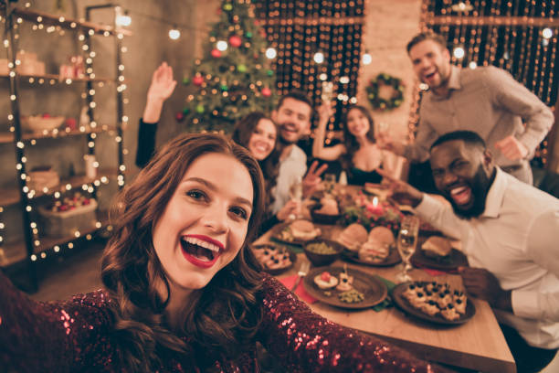 Close up photo of cheerful fellows in formal wear sit around table enjoy christmas party x-mas holidays making selfie in house full of noel decoration Close up photo of cheerful fellows in formal wear sit around table enjoy, christmas party x-mas holidays making selfie in house full of noel decoration dinner stock pictures, royalty-free photos & images