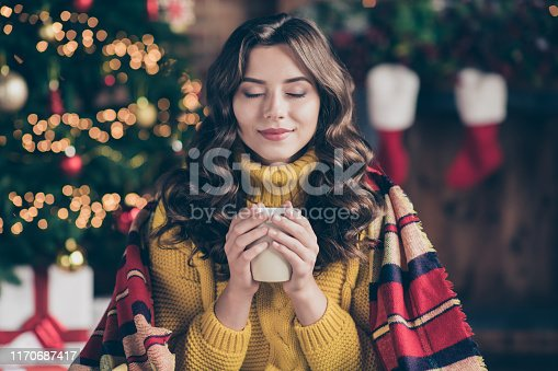 istock Close up photo of cheerful fun nice positive cute charming girl sensing nice smell of drink wearing yellow pullover sitting in plaid enjoying her carefree leisure with cup of tea 1170687417