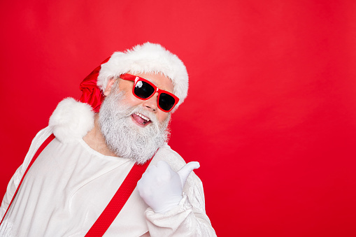 istock Close up photo of cheerful funny fat overweight style stylish trendy santa claus in eyewear pointing at copyspace recommend winter season sales isolated over red background 1175685921
