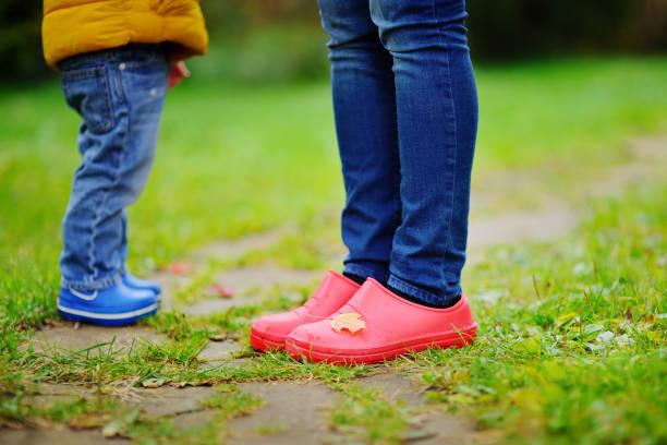 nahaufnahme foto von kind und erwachsenen beine in gummistiefeln - granny legs stock-fotos und bilder
