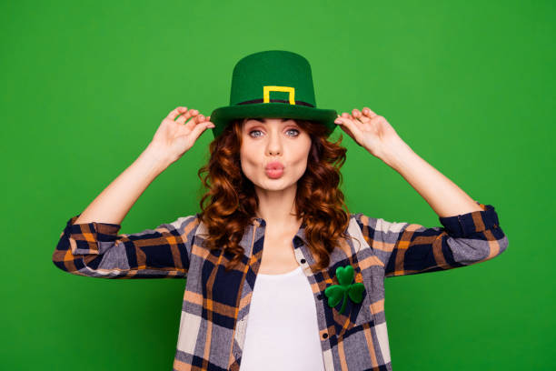 close up photo of cool attractive she her lady holding hands cap sending kiss to ireland people wearing casual checkered plaid shirt leprechaun headwear isolated on green bright vivid background - luck of the irish stock photos and pictures
