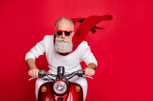 Close up photo of cool pensioner riding his bike with air wind blowing wearing white jumper sweater isolated over red background