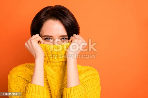 Close up photo of cute nice, charming girl hiding from cold by wrapping up in collar while isolated with orange background