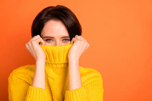 close up photo of cute nice charming girl hiding from cold by wrapping up in collar while isolated with orange background - donna si nasconde foto e immagini stock
