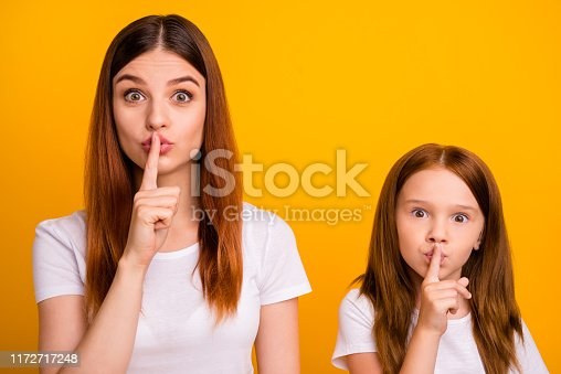 Close up photo of cute people with long, ginger hair saying hush wearing white t-shirt isolated over yellow background