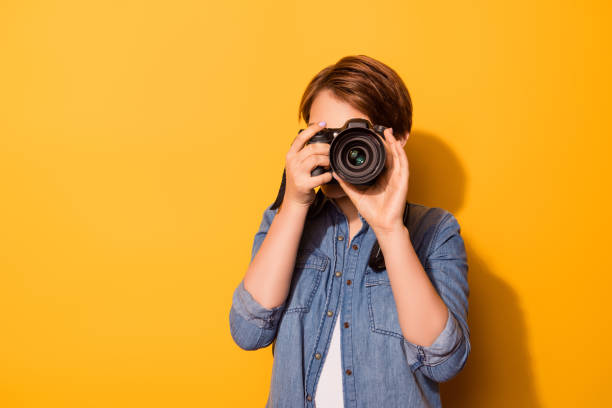close up photo of female photographer photographing with a camera in casual clothes on the bright yellow background - fotograf zdjęcia i obrazy z banku zdjęć