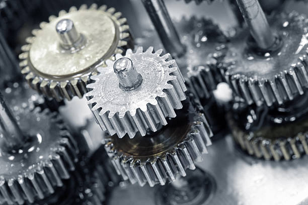 Close up photo of gears and wheels Macro picture of small gear wheels inside a machine. A gear or cogwheel is a rotating machine part having cut teeth, or cogs, which mesh with another toothed part to transmit torque, in most cases with teeth on the one gear being of identical shape, and often also with that shape on the other gear. Geared devices can change the speed, torque, and direction of a power source.  mechanical engineering stock pictures, royalty-free photos & images