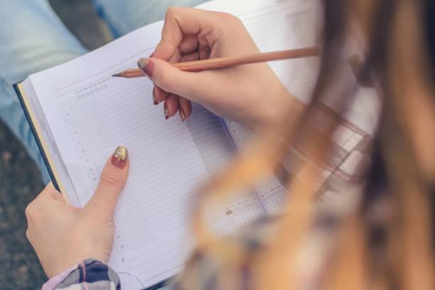 nahaufnahme foto von mädchenhänden schreiben komposition in ihr tagebuch - trainingstagebuch stock-fotos und bilder