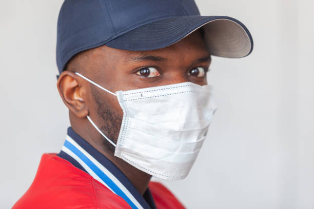 Close up photo of handsome african man in a cap and casual clothes wearing medical mask shocked with coronavirus 2019 danger stock photo