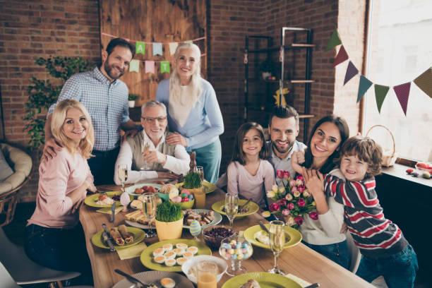 close-up fotografia de grande empresa reunidos sentado com flores tulipas abraços champanhe toothy smiles páscoa ovos alegria decorações de semana férias férias em família - familia pascoa - fotografias e filmes do acervo