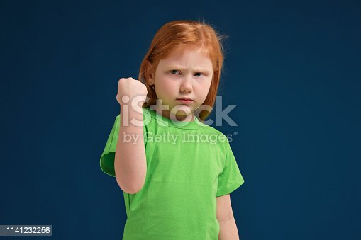 close-up portrait of redhead emotional little girl in green t-shirt on blue background. She is about to get nervous, threaten with her fist