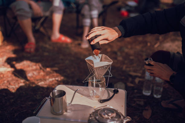 Close up photo of man preparing coffee at camping in forest stock photo