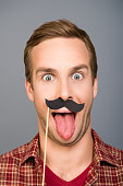 Close up photo of man with paper mustache showing tongue