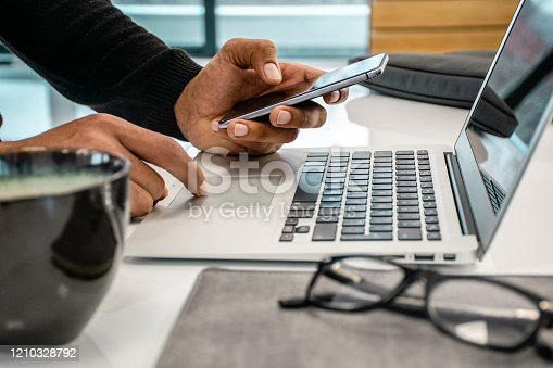 Close up photo of men using phone and laptop in the office