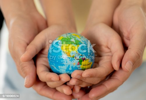 istock close up photo of mother and child holding hands with a world globe in their hands in better world idea protection and education concept 979996524