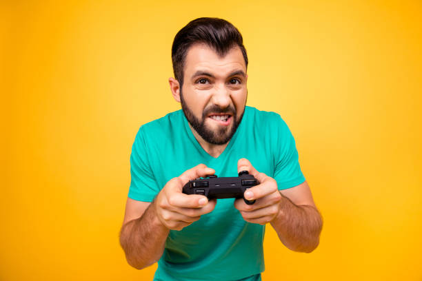 close up photo of nervous scary fan of video games, he is holding a console, isolated on bright yellow background, copyspace - soccer supporter portrait imagens e fotografias de stock