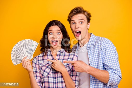 Close up photo of pair pack of bucks in hands he him his she her lady boy mouth opened luck shouting showing fingers on money wearing casual plaid shirts outfit isolated on yellow orange background.