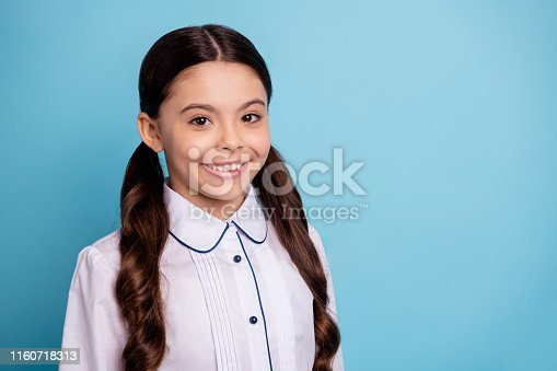 Close up photo of pretty kid looking feeling, glad isolated over blue background