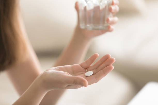 Close up photo of round white pill in female hand stock photo