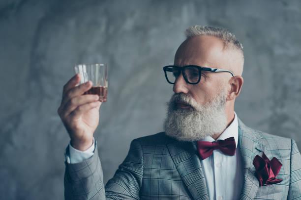 close-up foto van ernstig nadenkend zeker tevreden bebaarde rijke rijke ondernemer wijn-maker fabrikant kijken naar het glas met whisky, geïsoleerd op een grijze achtergrond - tasting stockfoto's en -beelden