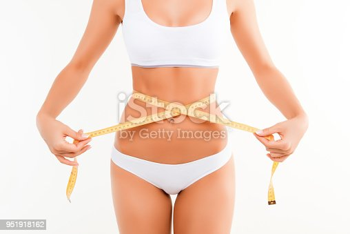 1125413862 istock photo Close up photo of sexy woman measuring her waist's size with tape measure 951918162