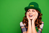 Close up photo of she her curly brunette arms on cheekbones looking to empty space admiring wear casual checkered plaid shirt leprechaun headwear isolated green vivid bright vibrant background