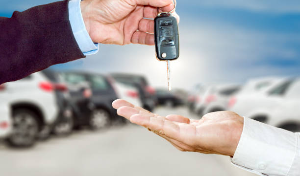 close up photo of the transfer of keys from the new machine to the buyer against the background of standing cars - used car selling stock pictures, royalty-free photos & images
