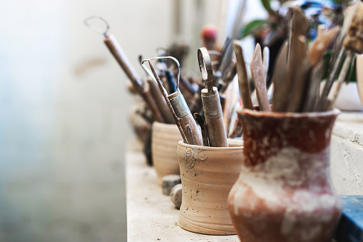 Close up photo of tools for ceramics work stand on window sill indoor workspace ready correct dishes or tableware form with copy space for text