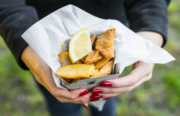 Close up photo of traditional fish and chips at a street food market Fish and chips with lemon in a paper cone food festival stock pictures, royalty-free photos & images