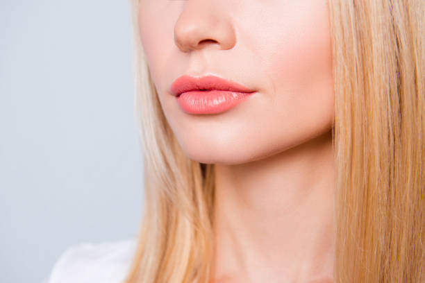 Close up photo of woman's skin with expression wrinkles, blonde hair and lips with moisturizing balm on them. She is isolated on grey background stock photo