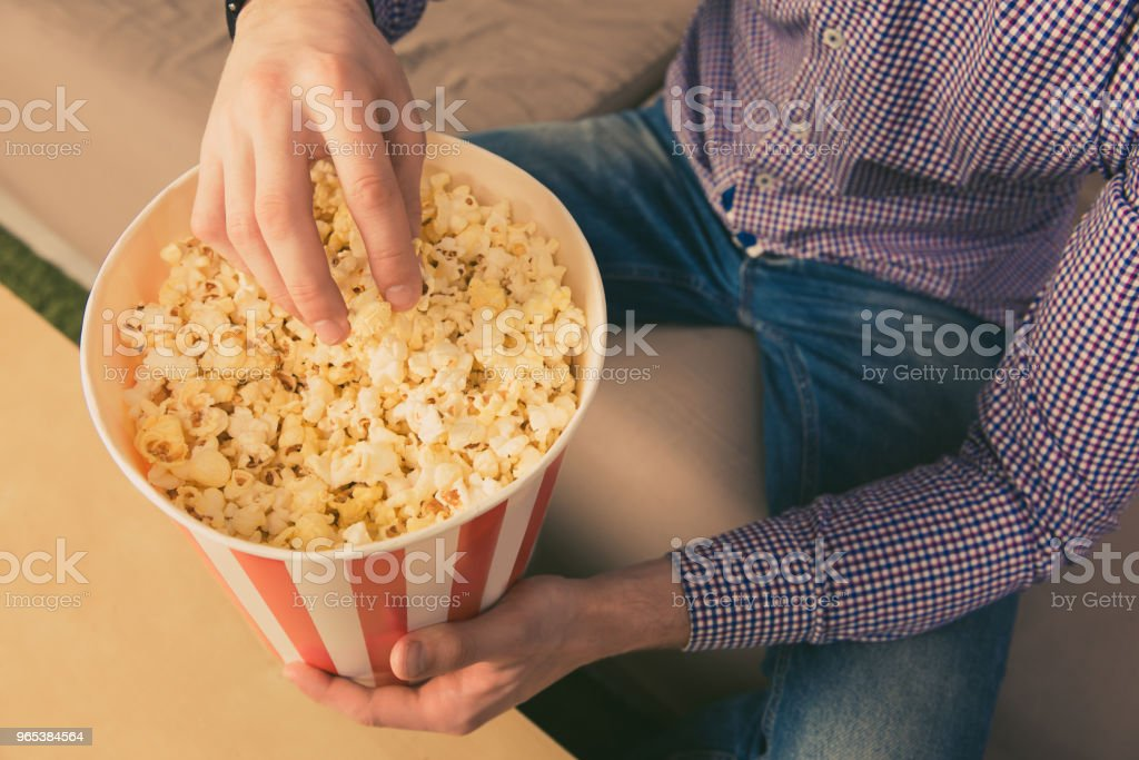 Close up photo of young man eating popcorn at home zbiór zdjęć royalty-free