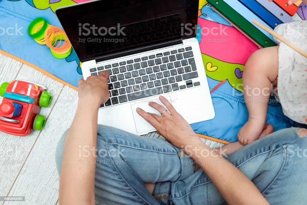 Close up photo of young mother working on laptop with her toddler child. Freelance business concept. Selective focus, top view stock photo