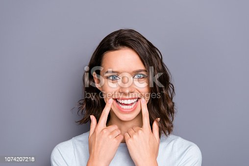 Close up photo portrait of cheerful glad positive lady with her brunette hair she demonstrate toothy wide hollywood smile isolated on gray background hold forefingers on two hand near mouth