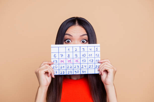 close up photo portrait of terrified amazed with big eyes lady closing covering she face with paper handmade calendar isolated on pastel beige background copy space - mestruazione foto e immagini stock
