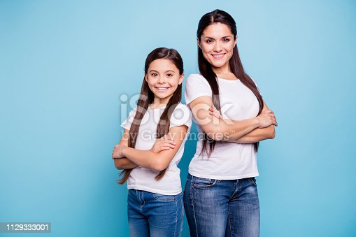 istock Close up photo pretty two people brown haired mum small little daughter crossed arms self-confidently stand back to back ready win winner family games wear t-shirts isolated bright blue background 1129333001