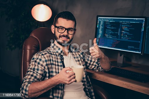 Close up photo stubble handsome he him his guy support programming, hands arms mug beverage thumb up coder code development outsource IT two monitors table office wear specs formalwear shirt