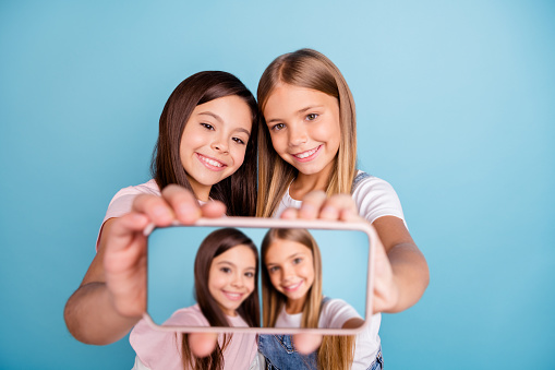 Close up photo two little she her blond brunette girls long pretty hair telephone make take selfies talk tell speak millennials wearing casual jeans denim t-shirts isolated blue bright background
