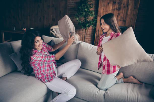 nahaufnahme foto zwei personen mama töchterchen spiellaune kissen kämpfen barfuß schrei shout tragen rosa karierten hemden wohnung zimmer sit liegende gemütliche couch sofa diwan - jubeln mutter shirts stock-fotos und bilder