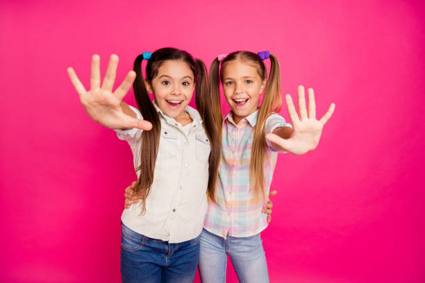 Close up photo two small little age she her girls hands arms palms counting fingers school lesson class wearing casual jeans denim checkered plaid shirts isolated rose vibrant vivid background stock photo