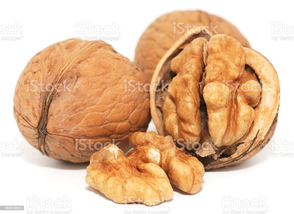 Close up photograph of three walnuts, one cracked open stock photo