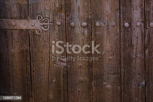 1124475954 istock photo Close up photography of a wooden door texture in dark brown color with old, rusted metal elements. 1035571264
