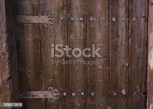 1124475954 istock photo Close up photography of a wooden door texture in dark brown color with old, rusted metal elements. 1035573976