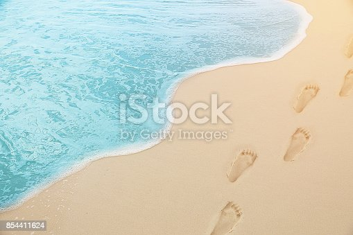 istock close up photography - Tropical Blue sea water coming on the white beach sand with footprint 854411624