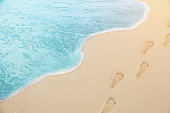 close up photography - Tropical Blue sea water coming on the white beach sand with footprint