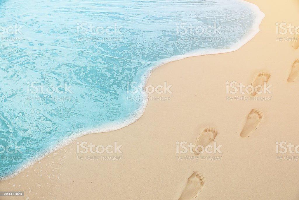close up photography - Tropical Blue sea water coming on the white beach sand with footprint stock photo