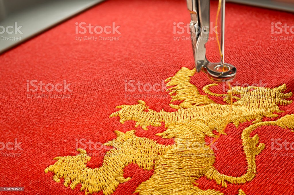 Gros plan photo broderie design or lion sur tissu rouge - Photo