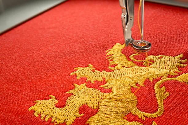 Cerca de León de oro de diseño cuadro bordado en tela roja - foto de stock